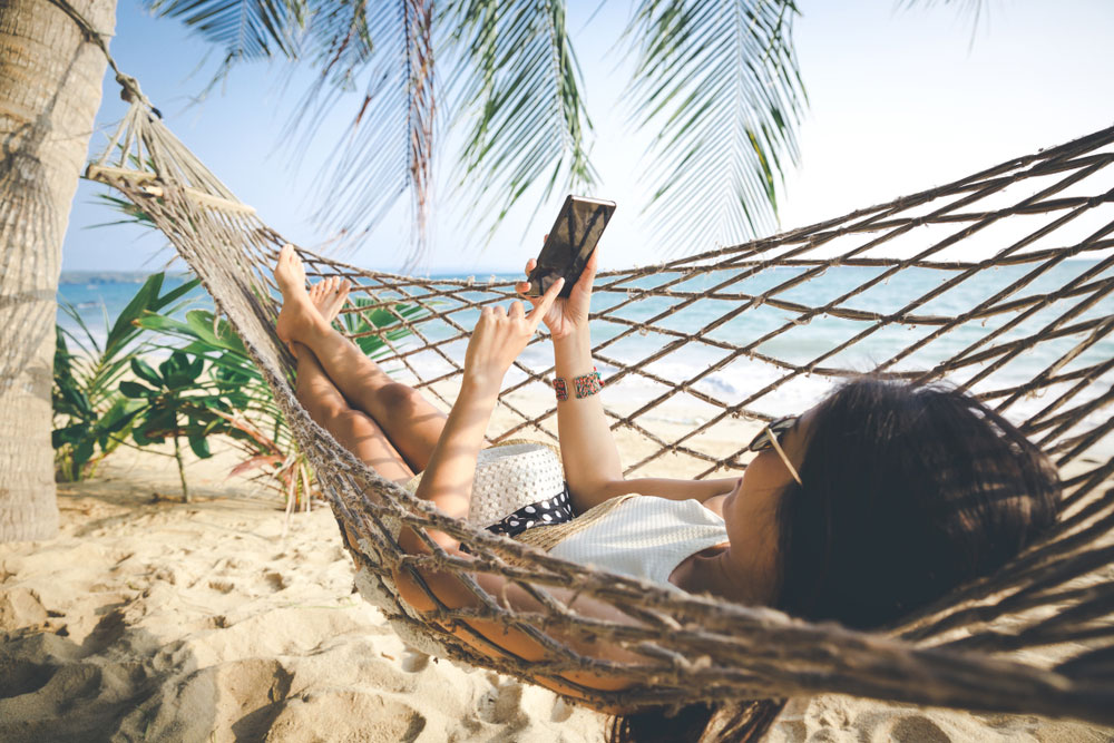 woman using her phone in a hammock